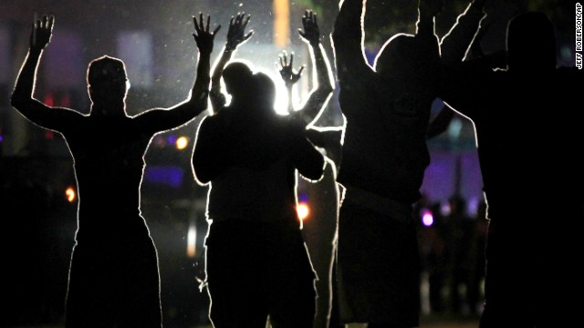 People raise their hands in the middle of the street as police wearing riot gear move toward their position trying to get them to disperse Monday, Aug. 11, 2014, in Ferguson, Mo. The FBI opened an investigation Monday into the death of 18-year-old Michael Brown, who police said was shot multiple times Saturday after being confronted by an officer in Ferguson. Authorities in Ferguson used tear gas and rubber bullets to try to disperse a large crowd Monday night that had gathered at the site of a burned-out convenience store damaged a night earlier, when many businesses in the area were looted. (AP Photo/People raise their hands in the middle of the street as police wearing riot gear move toward their position trying to get them to disperse Monday, Aug. 11, 2014, in Ferguson, Mo. The FBI opened an investigation Monday into the death of 18-year-old Michael Brown, who police said was shot multiple times Saturday after being confronted by an officer in Ferguson. Authorities in Ferguson used tear gas and rubber bullets to try to disperse a large crowd Monday night that had gathered at the site of a burned-out convenience store damaged a night earlier, when many businesses in the area were looted. (AP Photo/Jeff Roberson) )