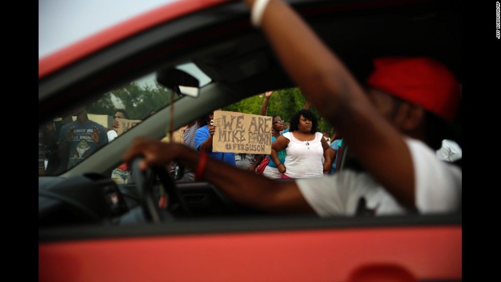 Demonstrators hold signs as traffic moves slowly past them on August 14, 2014.