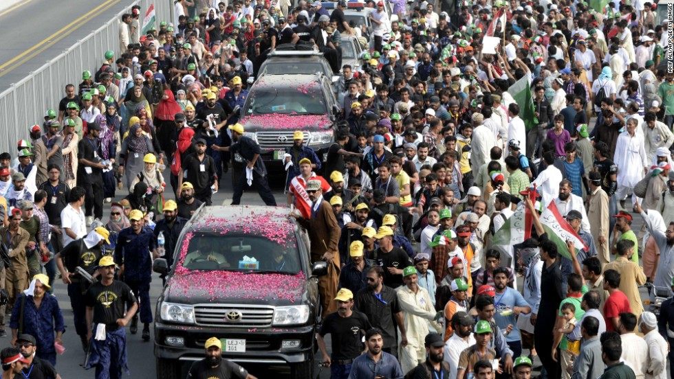 Followers of Tahir ul Qadri escort a vehicle carrying the cleric through Pakistan's eastern city of Lahore on August 14.