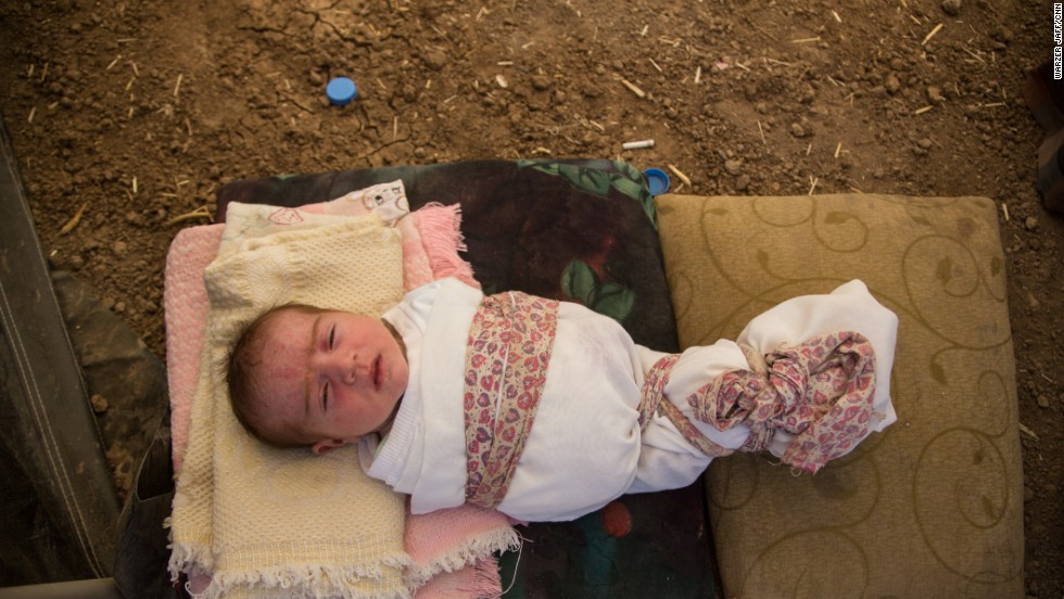 "This 6-day-old girl was born on Sinjar Mountain. Her mother might name her ""Hajar,"" meaning migrant or as the family interpreted it, ""Exile."""