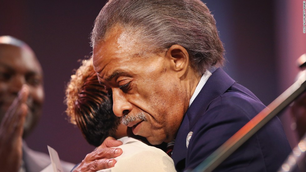 The Rev. Al Sharpton hugs McSpadden during the rally.