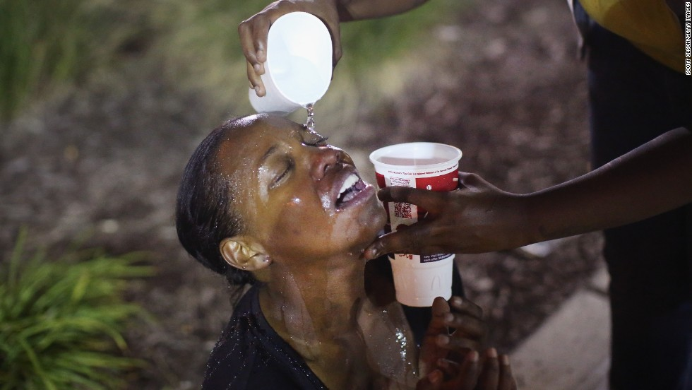 Water gets poured into a woman's eyes after a tear gas attack by police on August 17, 2014.