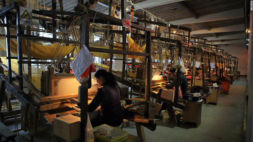 These four-meter-high machines are operated by two craftsmen at the same time -- one sits on top the machine sorting threads, the other sits at the opposite end and weaves. Each team can produce only five centimeters of yunjin per day.