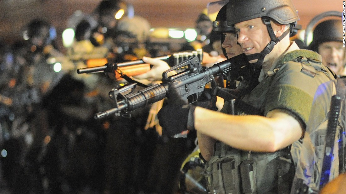 Officers stand with weapons drawn during a protest on West Florissant Avenue on August 18, 2014.