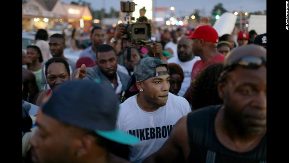 Musician Nelly, center, joins demonstrators in Ferguson on August 18, 2014.