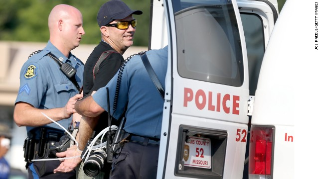 Getty Images staff photographer Scott Olson is placed into a paddy wagon after being arrested.