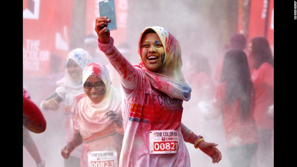 "A woman takes a selfie as she runs through a ""color station"" during the Color Run in Kuala Lumpur, Malaysia, on Sunday, August 17. The race, billed as <a href=""http://thecolorrun.com"" target=""_blank"">""the happiest 5K on the planet,""</a> involves lots of colored powder and takes place in different cities worldwide throughout the year."