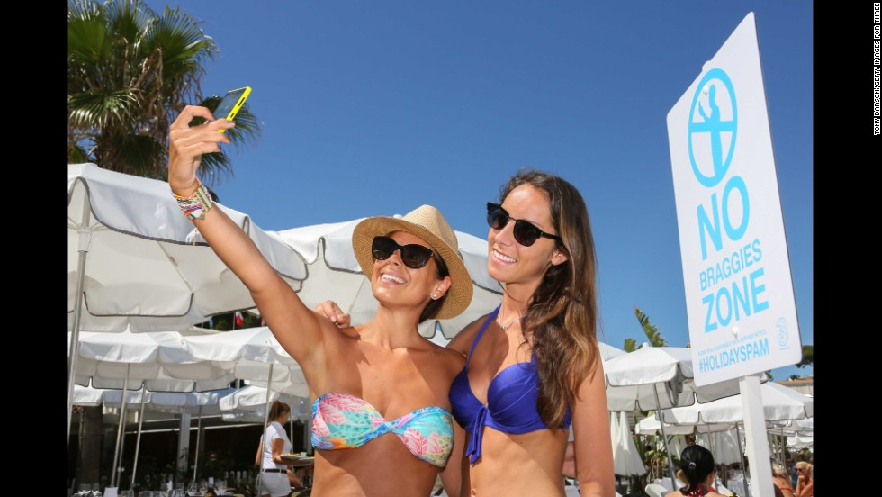 """Two British women take a selfie on France's Garoupe Beach on Thursday, August 14, in front of a sign telling people not to take """"holiday braggies."""""""
