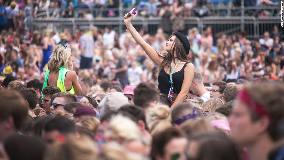 A festivalgoer takes a selfie during a V Festival concert Saturday, August 16, in Chelmsford, England.