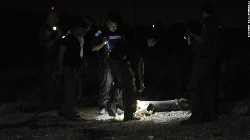 Police examine the remains of a rocket launched from Gaza that landed near the kibbutz of Yad Mordechay on August 19.