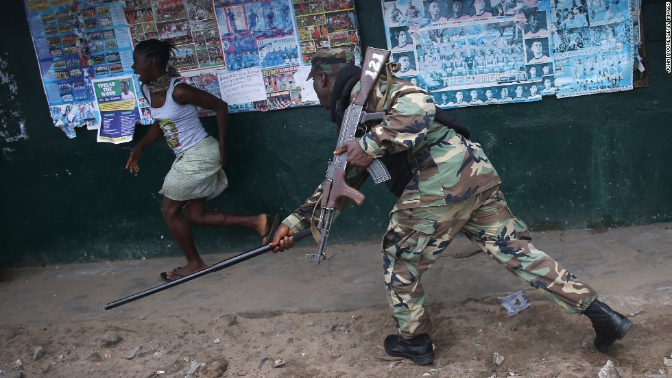 An Ebola Task Force soldier beats a local resident while enforcing a quarantine in the West Point slum of Monrovia, Liberia, on Wednesday, August 20. The Ebola virus has killed more than 1,350 people in West Africa since March, according to the World Health Organization.