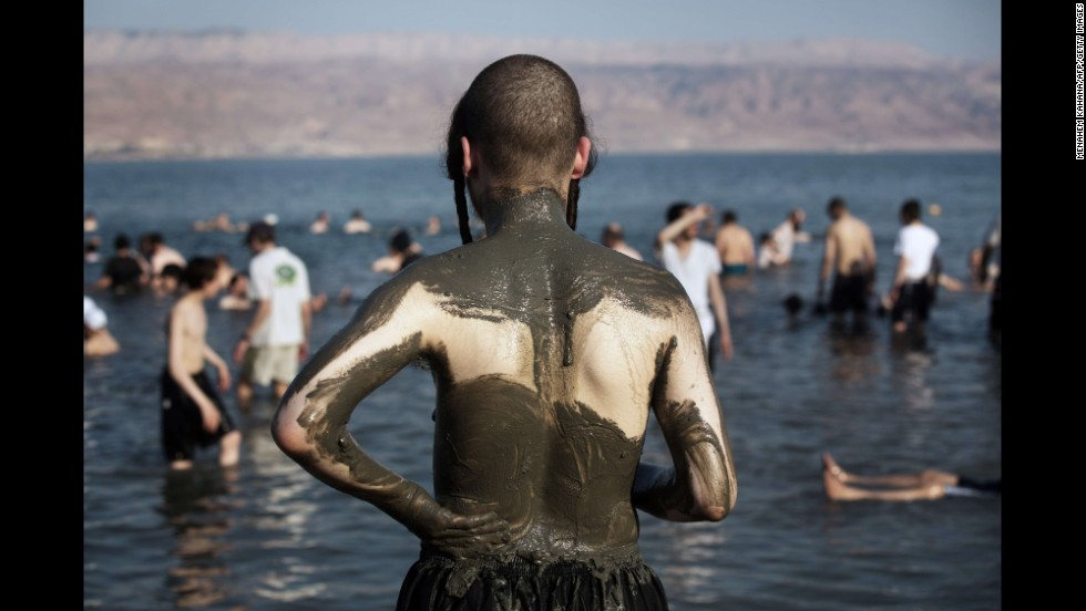 Ultra-Orthodox Jewish men and boys cover their bodies with mineral-rich mud on the shores of the Dead Sea during their vacation Sunday, August 17, at a beach in the West Bank.