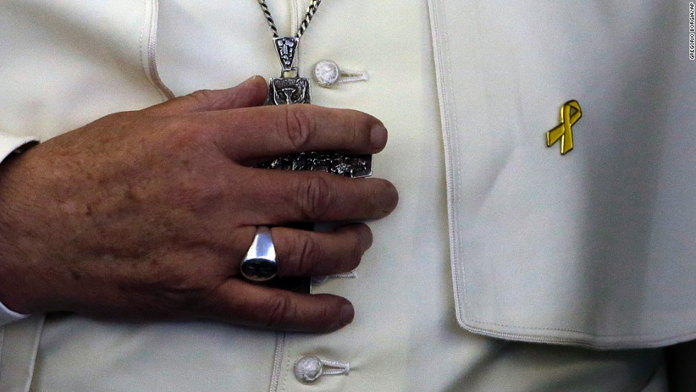 "A yellow ribbon, donated by one of the relatives of the <a href=""http://www.cnn.com/2014/04/15/asia/gallery/south-korea-sinking-ship/index.html"">Sewol ferry disaster</a>, is seen on Pope Francis' mantle as he meets the media Monday, August 18, after <a href=""http://www.cnn.com/2014/08/13/asia/gallery/pope-francis-south-korea/index.html"">his tour of South Korea.</a> It was the first papal visit to South Korea since Pope John Paul II went there 25 years ago."