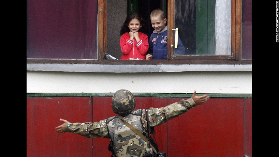 A Ukrainian soldier gestures as he talks with children Monday, August 18, in Popasna, a Ukrainian city recently held by pro-Russian rebels.