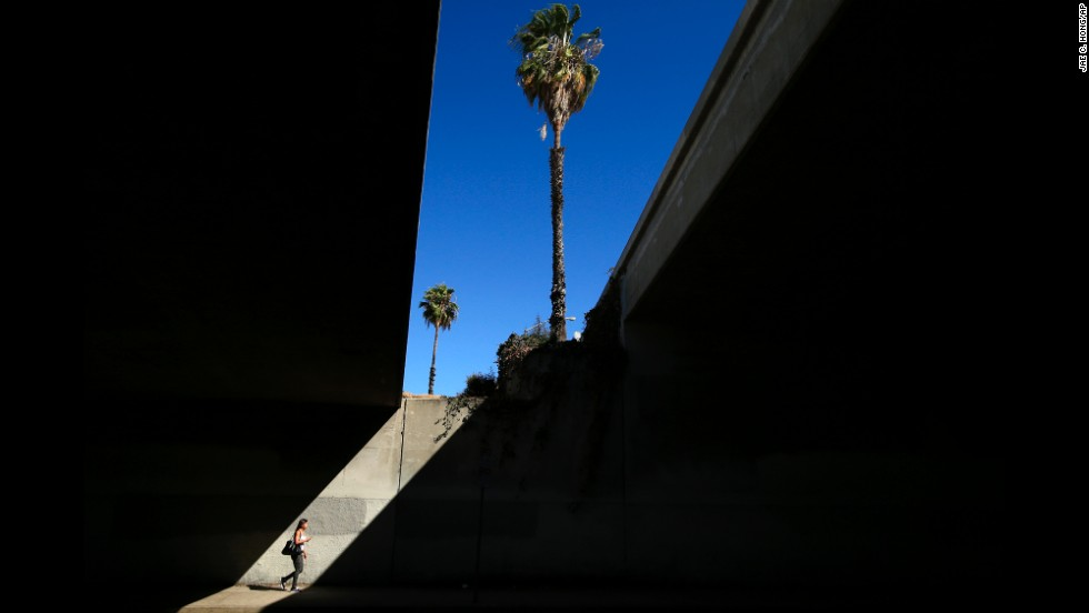 A woman walks under the 101 Freeway in Los Angeles on Friday, August 15.