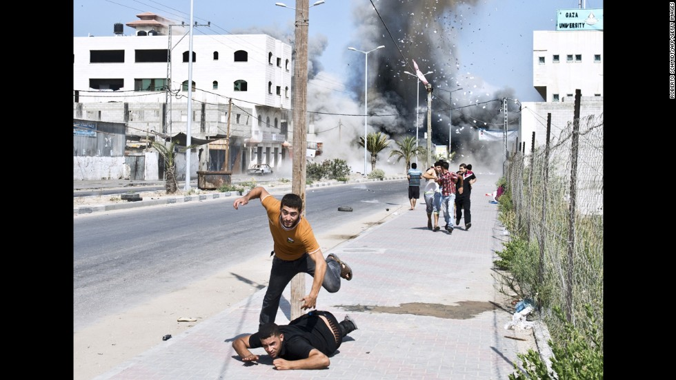 Palestinians run away from debris after a bomb from an Israeli airstrike hit a house in Gaza on Saturday, August 23.