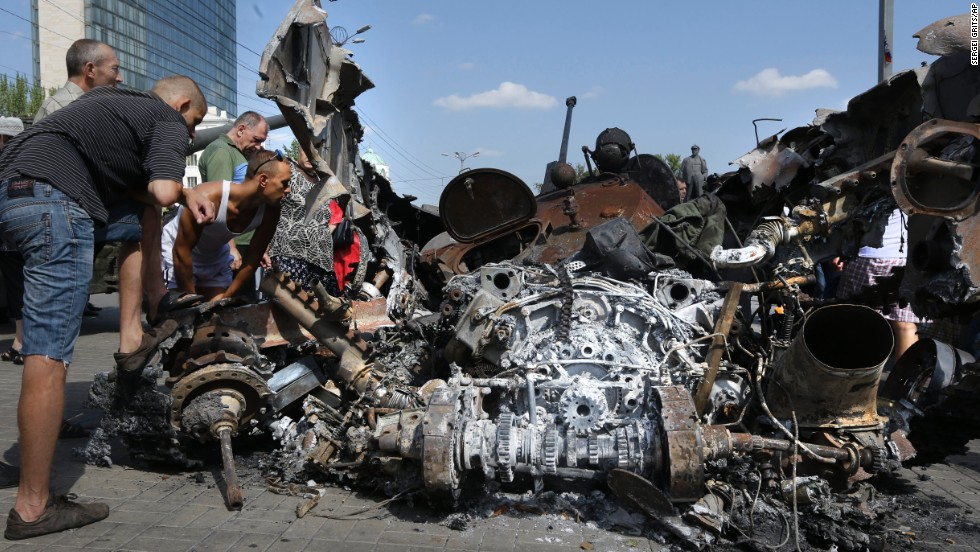 People look at damaged Ukrainian military equipment in Donetsk on August 24.