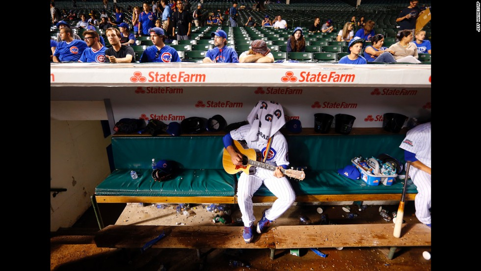 Chicago Cubs backup catcher John Baker, center, plays guitar during a rain delay in the fifth inning against the San Francisco Giants at Wrigley Field in Chicago on Tuesday, August 19.