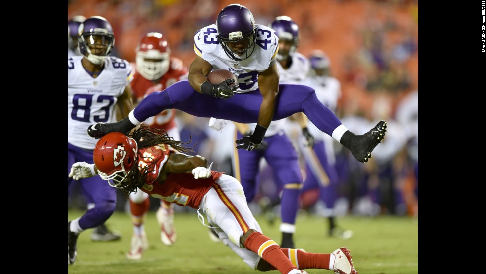 Dominique Williams of the Minnesota Vikings leaps over Jerron McMillians of the Kansas City Chiefs on Saturday, August 23, at Arrowhead Stadium in Kansas City, Missouri.