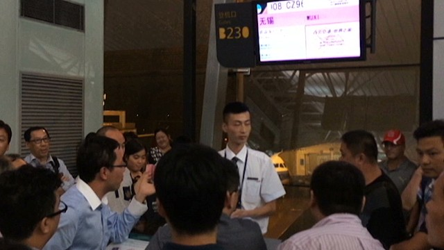 Frustrated travelers confront a gate agent at Baiyun International Airport.