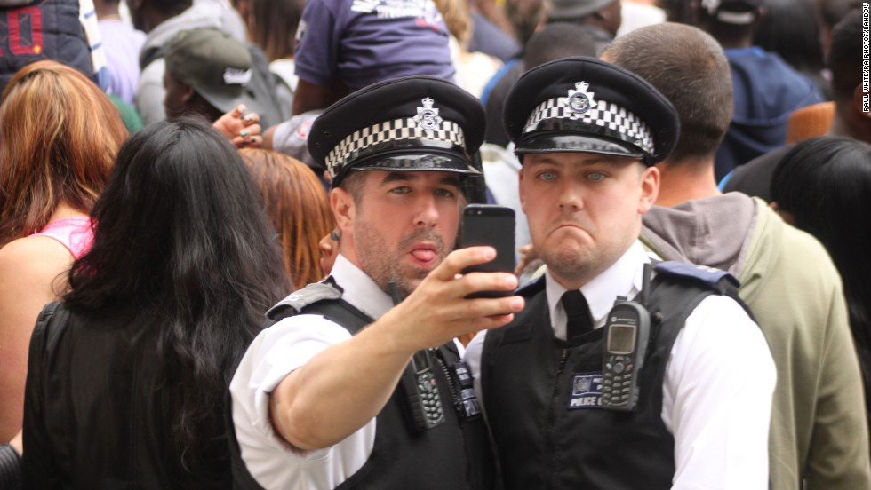 Police officers take a selfie during the Notting Hill Carnival family day in  London on Sunday, August 24.