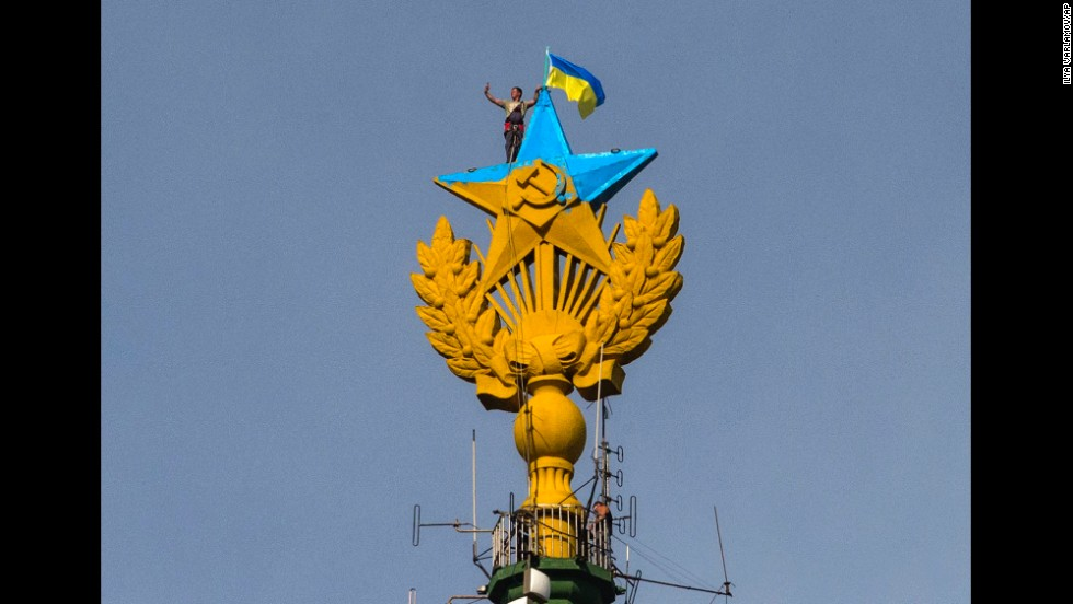 A worker takes a selfie before removing a yellow and blue Ukrainian flag attached by protesters atop a Stalin-era skyscraper in Moscow on Wednesday, August 20. Protesters scaled the skyscraper and painted the Soviet star on its spire in the national colors of Ukraine. The dangerous prank, which set Russian social networking sites abuzz, drew a harsh response from the police.