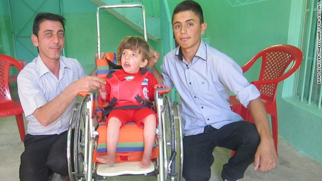 Azwan, right, used to help deliver wheelchairs for disabled Iraqi kids.