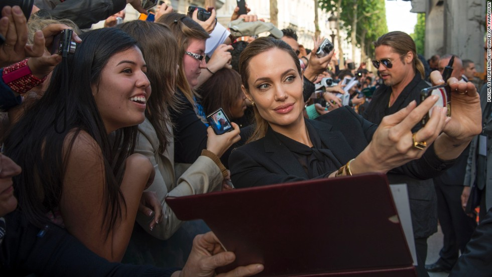 "Jolie takes a selfie with fans at the premiere of Pitt's ""World War Z"" in Paris in June 2013."