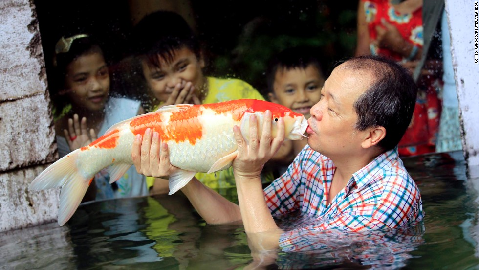 Zoo owner Manny Tangco kisses a Japanese Koi carp while children watch on Friday, August 22, in Malabon, a city north of Manila in the Philippines.