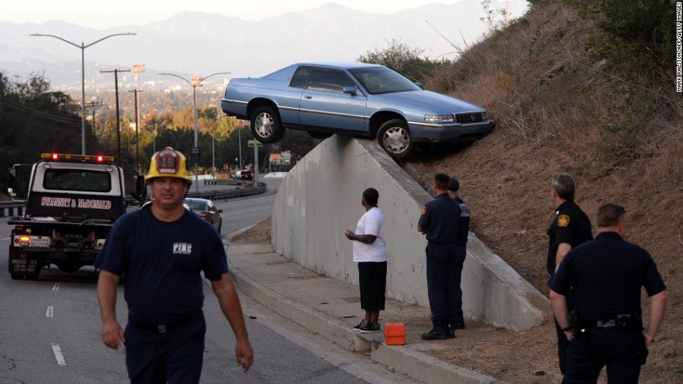 A car sits atop an embankment after its driver lost control and skidded up the concrete retaining wall in Los Angeles on Sunday, August 24. The driver and his passenger escaped injury.