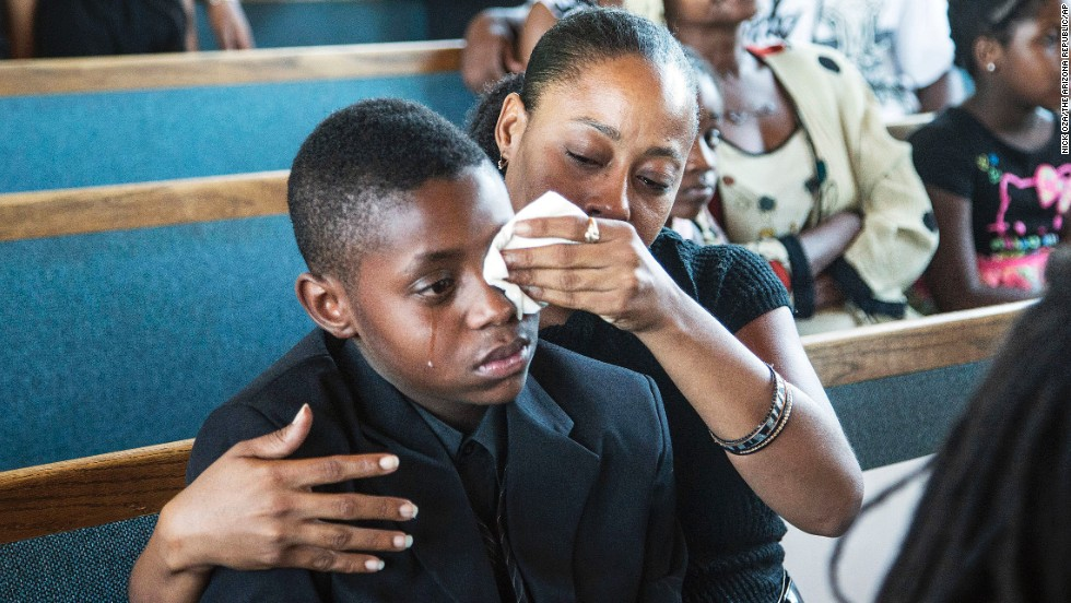 Sharon Lamb wipes tears from her 10-year-old son Kasai Hayden's face during the funeral for Michelle Cusseaux in Phoenix, Arizona, on Saturday, August 23. Cusseaux, 50, was shot earlier this month after she threatened officers with a claw hammer, authorities said. They were at her apartment to carry out an emergency court order to take her to a mental health facility.