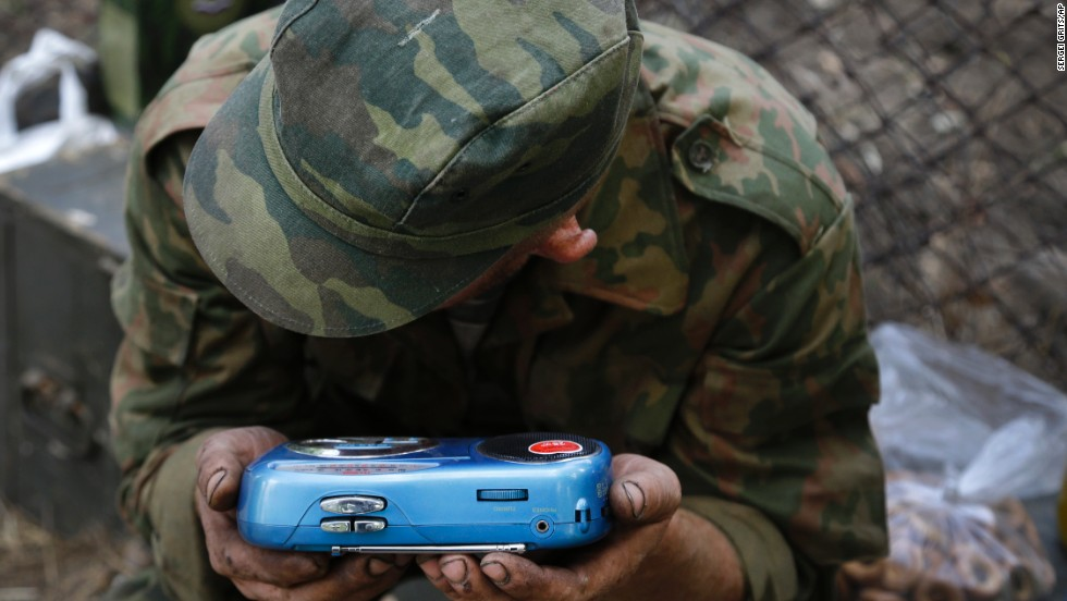 A pro-Russian rebel listens to the news on a transistor radio in the town of Novoazovsk, Ukraine, on Friday, August 29.