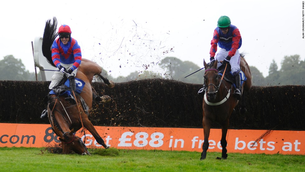 Tony McCoy, riding Rendl Beach, falls during a steeplechase race Thursday, August 28, at the Fontwell Park Racecourse in Fontwell, England. The 32Red Beginners' Chase was won by Will Kennedy, right, aboard Leath Acra Mor.