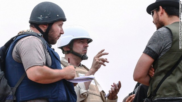 In this handout image made available by the photographer American journalist Steven Sotloff, left, talks to Libyan rebels on the Al Dafniya front line in Misrata, Libya, in June 2011.