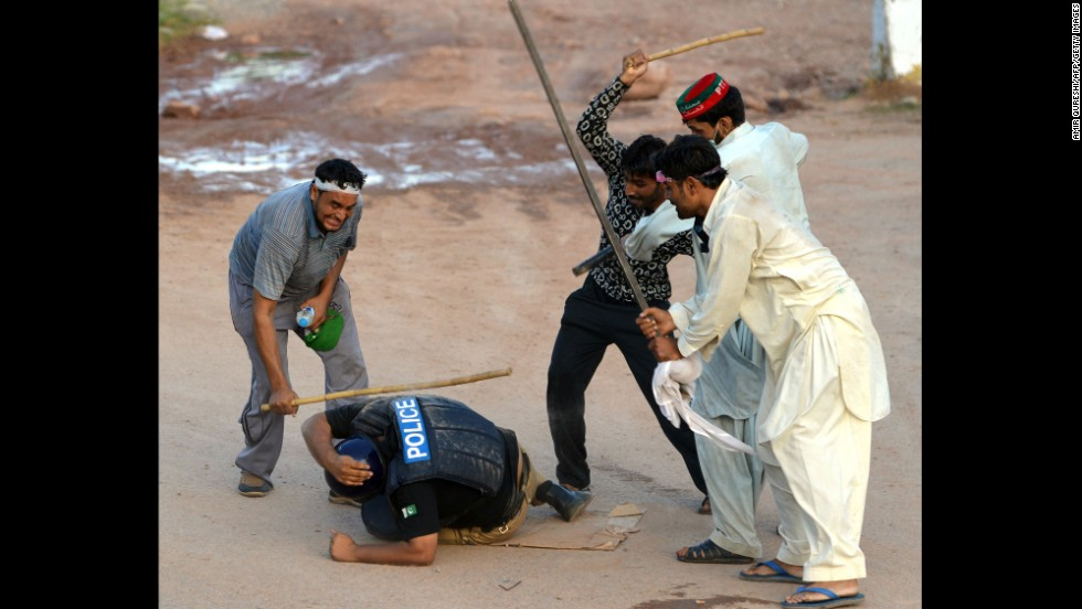 "Supporters of politician Imran Khan and cleric Tahir ul-Qadri beat a riot policeman during an anti-government protest in Islamabad, Pakistan, on Monday, September 1. Thousands of protesters, demanding the resignation of Pakistani Prime Minister Nawaz Sharif, <a href=""http://www.cnn.com/2014/09/01/world/asia/pakistan-protests/index.html"">have been battling police and soldiers</a> for weeks."