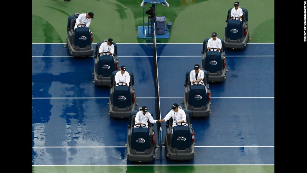 Workers at the U.S. Open tennis tournament dry a rain-soaked court Sunday, August 31, in New York.