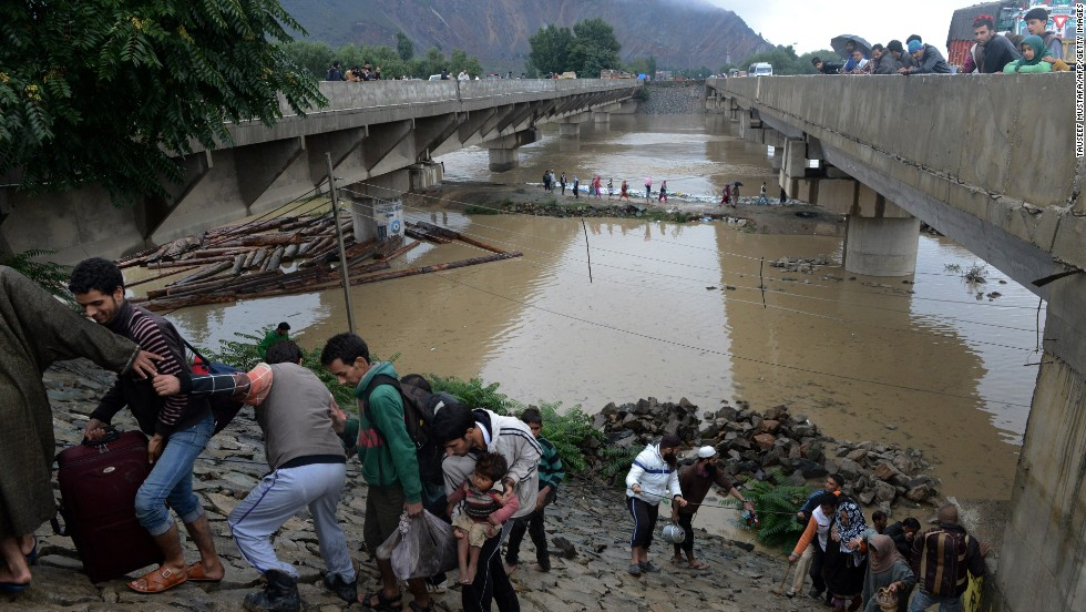 Residents walk along an embankment on the outskirts of Srinagar on September 6.