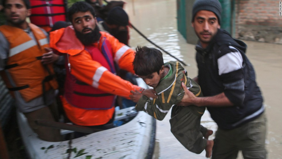 Volunteers help a child from a flooded area in Srinagar on Saturday, September 6.