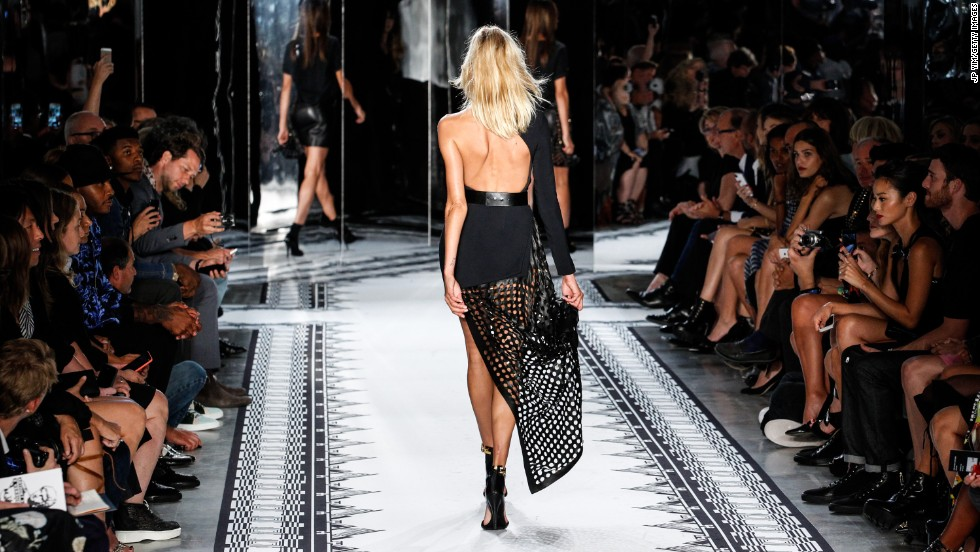 A model highlighted a dress's perforated leather detailing during the Versus Versace show.