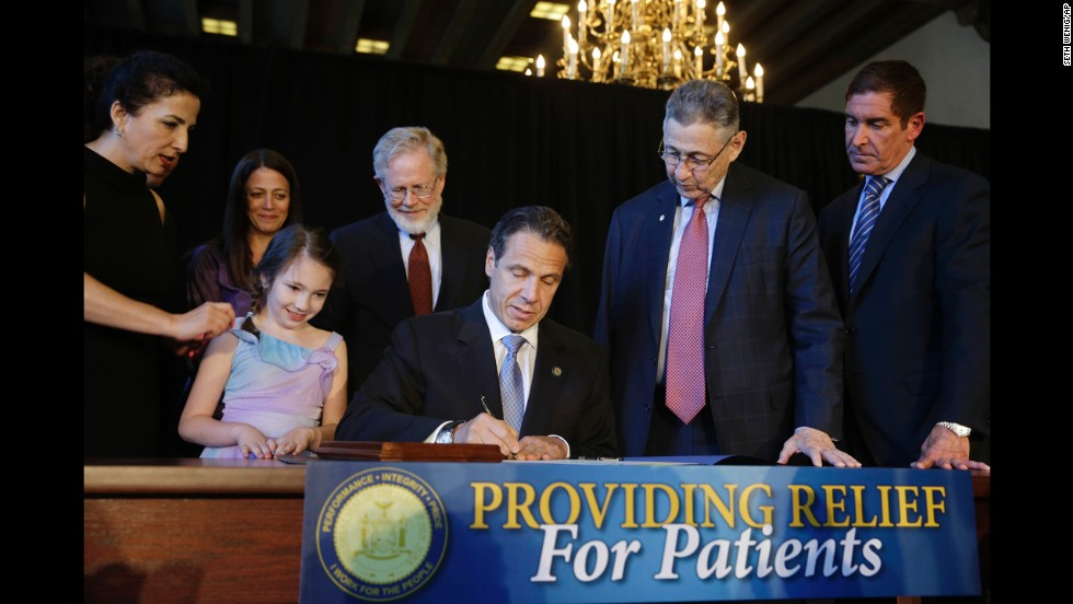 While politicians and supporters look on, New York Governor Andrew Cuomo signs a ceremonial bill to establish a medical marijuana program in New York, on July 7, 2014. New York is the 23rd U.S. state to authorize medical marijuana.