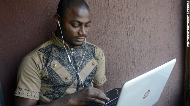 TO GO WITH STORY BY ADEROGBA OBISESAN Twenty five-year-old Computer Science undergraduate Kayode Sowole holds a laptop looking at his application in Lagos on April 10, 2014. The computer science student of University of Lagos is the brains behind a series of new smartphone applications to make the word of God available in the country's four main languages at the touch of a button. With this innovation, you do not need the Internet to read the Bible, neither do you need to bring a Bible to church. 'You have it in the local language of your choice on your phone.' AFP PHOTO / PIUS UTOMI EKPEI (Photo credit should read PIUS UTOMI EKPEI/AFP/Getty Images)