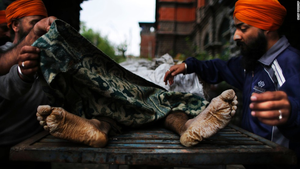 Kashmiri Sikhs cover the body of an Indian businessman whose body was fished out from floodwaters in Srinagar on September 12.