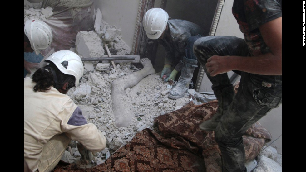 Residents of Aleppo remove a body from debris on Friday, August 29, after what activists claim was shelling by forces loyal to al-Assad.