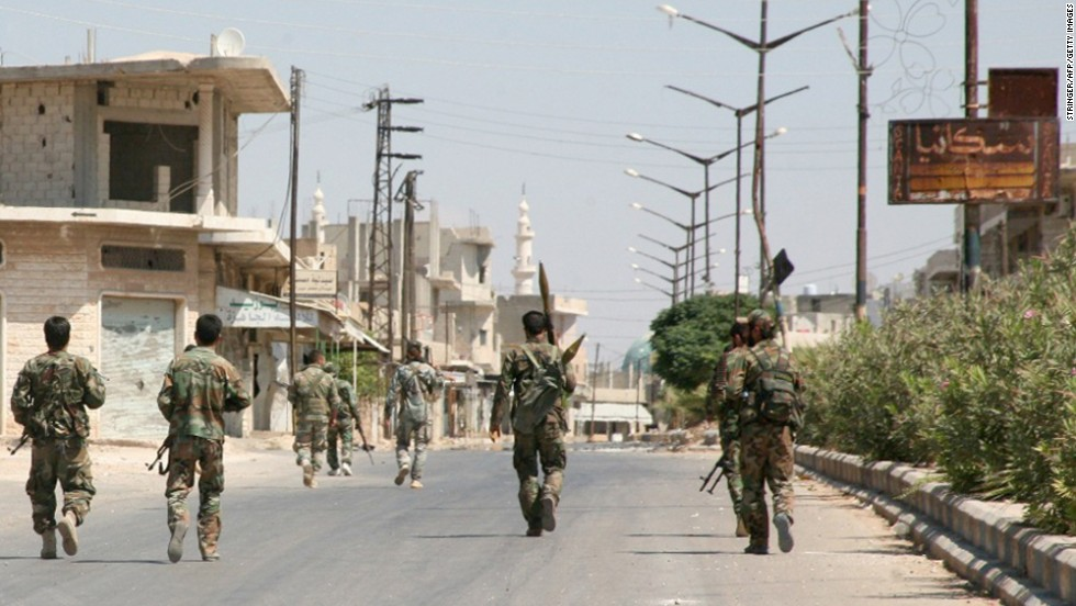 Syrian government forces walk down a street in Halfaya, Syria, after taking the city from rebel forces on Friday, September 12.