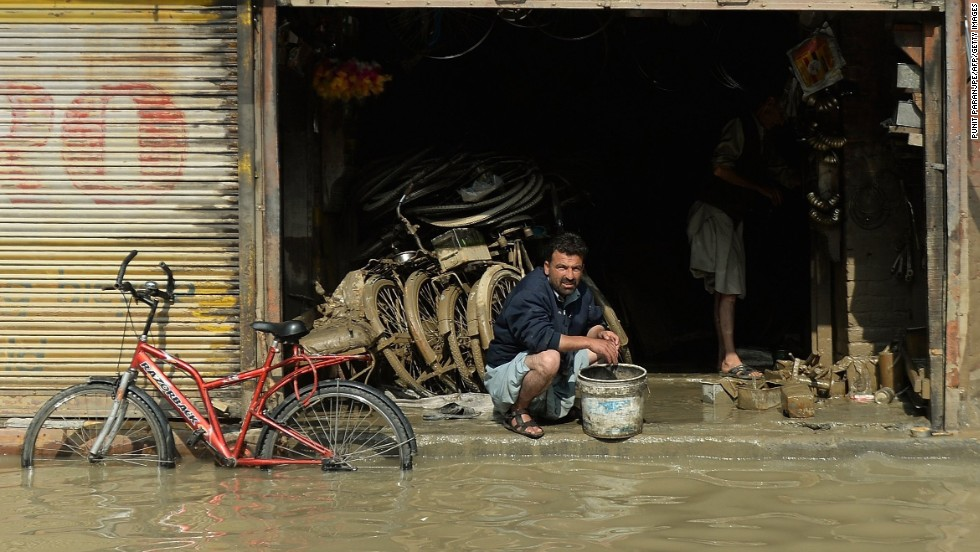 A Kashmiri shopkeeper looks on from his bicycle store as floodwaters recede in Srinagar on September 13.