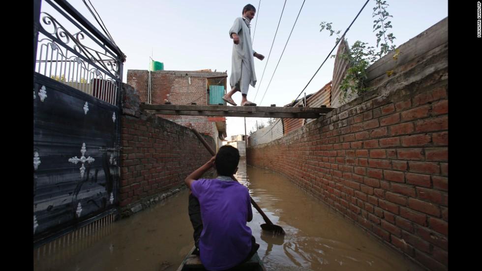 A boy rows a boat as his neighbor walks on a makeshift foot bridge in Srinagar on September 14.