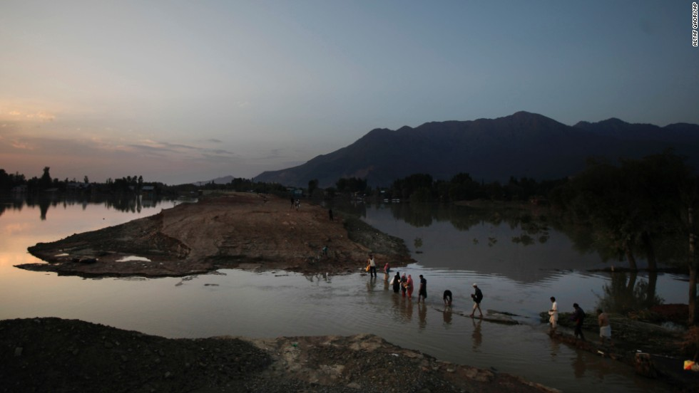 Flood victims wade through receding waters near Srinagar after collecting relief material on September 14.