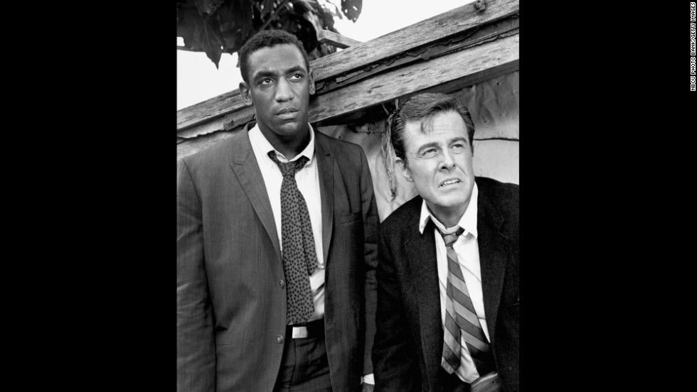 "Cosby won three Emmys for his portrayal of Alexander Scott, an Oxford-educated spy who travels undercover as a trainer with his tennis-playing partner, Kelly Robinson (Robert Culp) in ""I Spy,"" which aired on NBC from 1965 to 1968. Cosby was the first African-American to star in an American dramatic series."