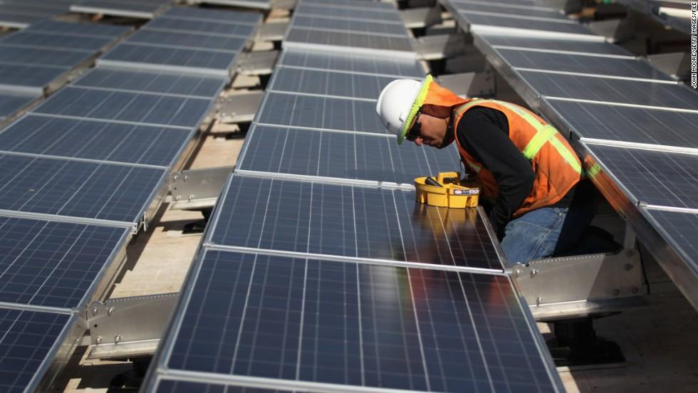 Construction Worker Checks Panels At Solar Panel Facility