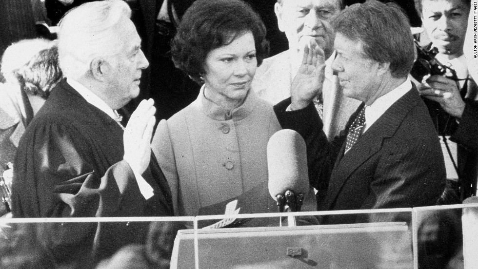 Chief Justice Warren Burger swears Carter into office on January 20, 1977, while Rosalynn Carter looks on.